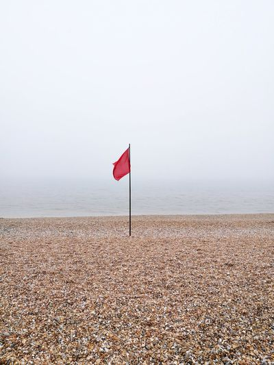 Red Flag Danger Red Flag Red No Swimming Day Calm Water Misty Morning Mist Seaside Flag Red Beach Sky Landscape Horizon Over Water Seascape Shore Tide Surf Coastline Rocky Coastline Coast Calm