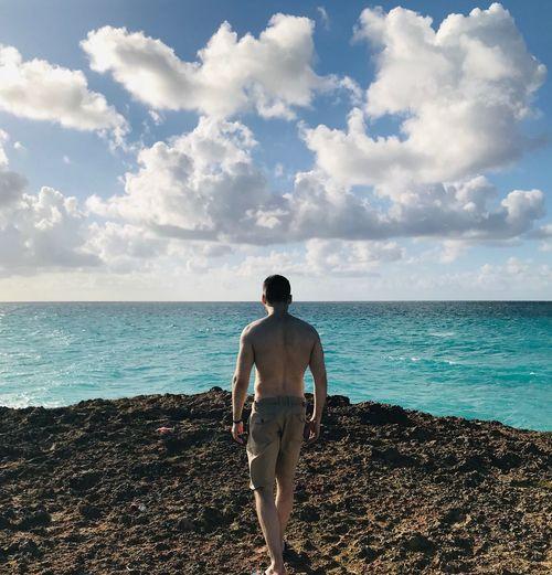 Rear view of shirtless man walking at beach