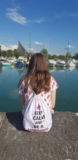 Rear view of girl on shore against sky