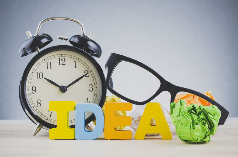 Creative and innovation concept, Alphabet word IDEA on wooden desk over dark background Still Life Studio Shot Indoors  Number No People Clock Time Close-up Alarm Clock Table Communication Group Of Objects White Background Yellow Choice Wall - Building Feature Green Color Variation Large Group Of Objects Metal