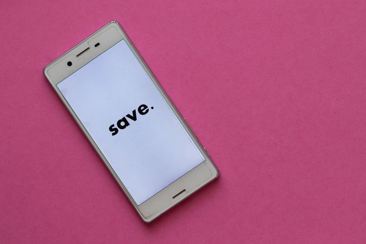 High angle view of smart phone on pink background