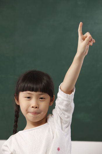 Close-up of girl with hand raised standing against blackboard