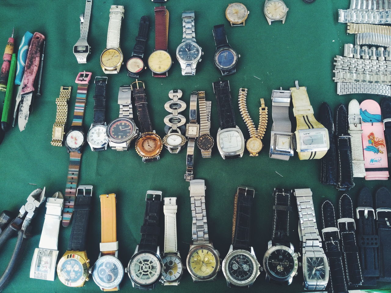 large group of objects, variation, choice, high angle view, still life, no people, arrangement, indoors, collection, abundance, wristwatch, order, for sale, time, watch, equipment, bottle, side by side, table, in a row