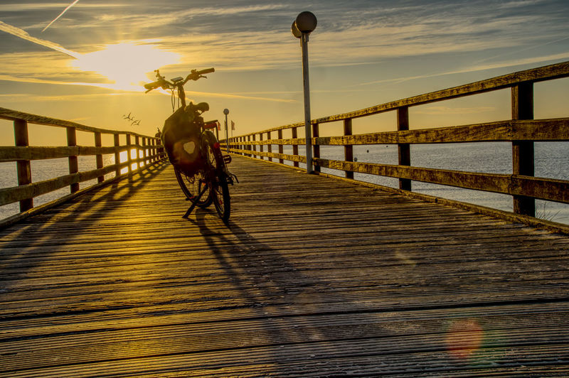 View of horse riding motorcycle on bridge against sky during sunset