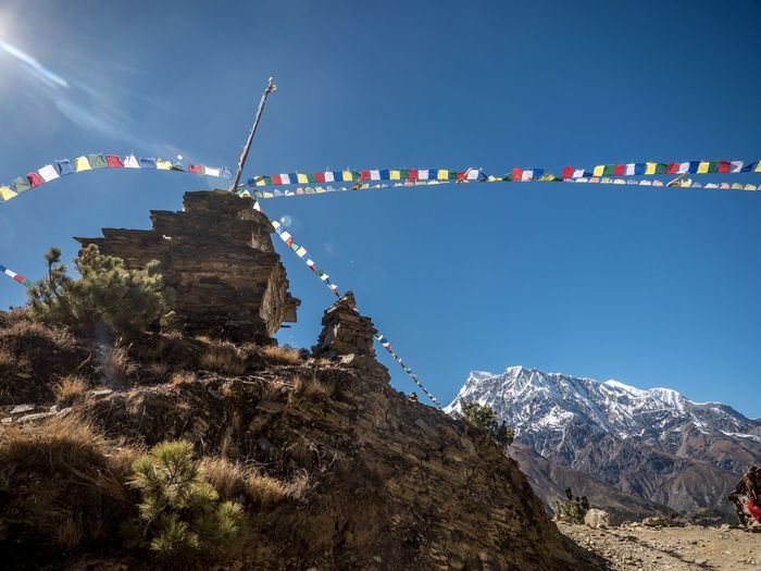 Low angle view of flags on mountain against sky