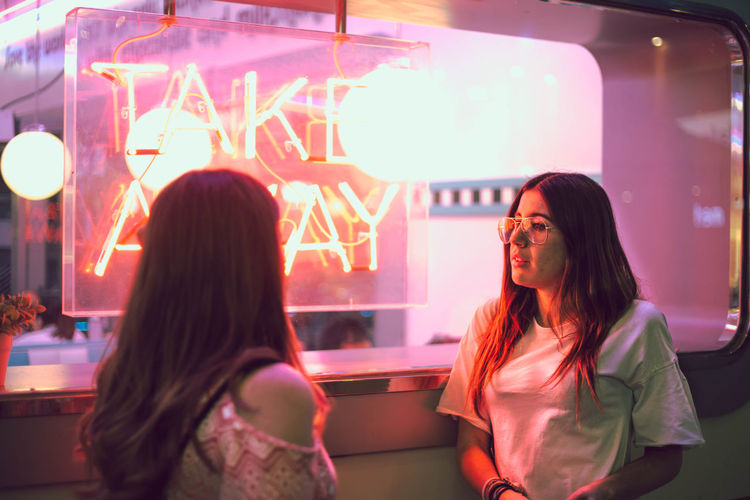 two young women talking next to a club with a window with neon lights Neon Neon Lights Women Two People Adult Illuminated Long Hair Hairstyle Togetherness Lifestyles Leisure Activity Night People Indoors  Hair Headshot Standing Young Women Real People Arts Culture And Entertainment Emotion Casual Clothing Positive Emotion Couple - Relationship
