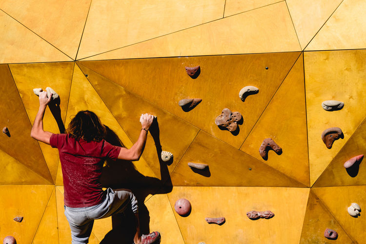 Rear view of woman climbing on yellow wall