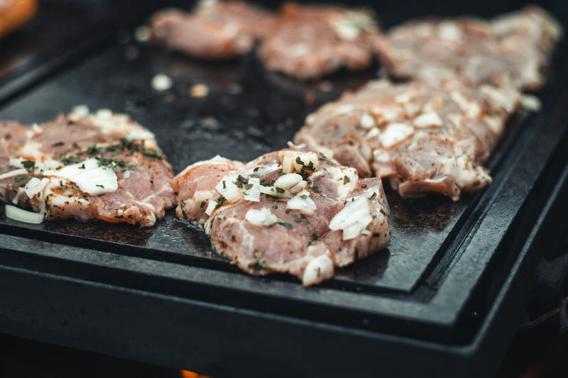 Man uses a steel ladle to turn a loaded pork neck with basil, salt, pepper and oil