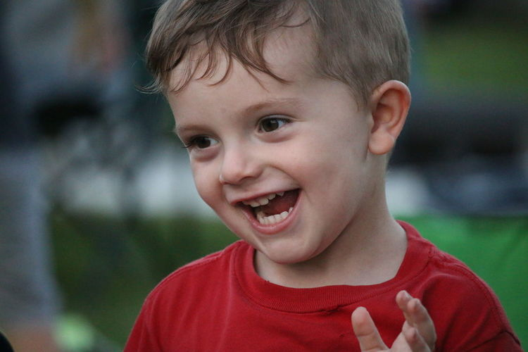 Close-up of cheerful boy standing at park