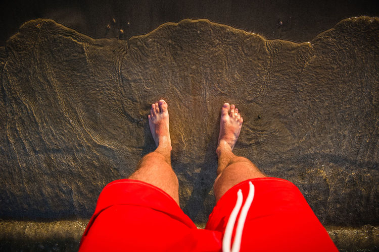 Man's feet in the sand, sea waves approaching beach Foot Freedom Man Pebble Beach Barefoot Beach Coast Concept Day Feet Hairylegs  Human Body Part Human Leg Low Section Nature Ocean One Person Red Swimsuit Relaxation Resort Sand Sea Summer Vacation Water