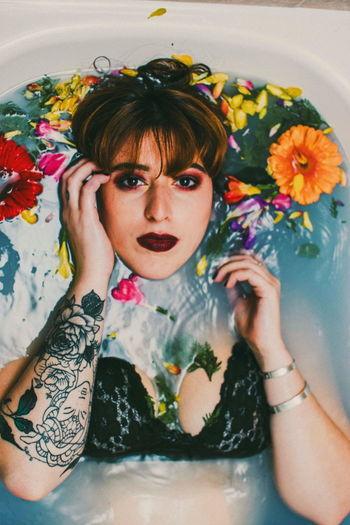 Portrait Of Beautiful Woman With Flowers In Bathtub