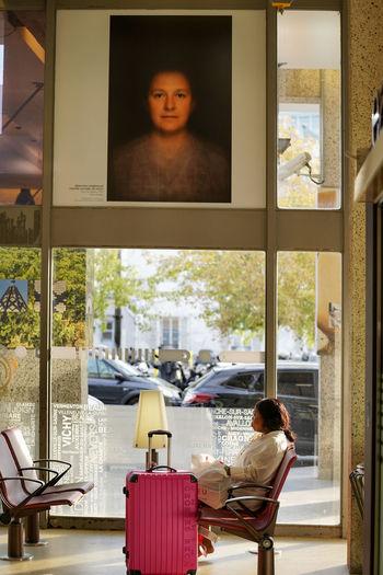 Portrait of man sitting on chair in glass window