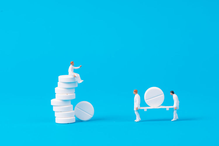 miniature people with white medical drug on blue background,health concept Doctor  Drug Hospital PainKiller Pharmacist Pharmacy Therapy Antibiotic Blue Background Figurine  Health Care And Medical Illness Medical Miniature People Patient Pharmaceutical Pill Sick Treatment White