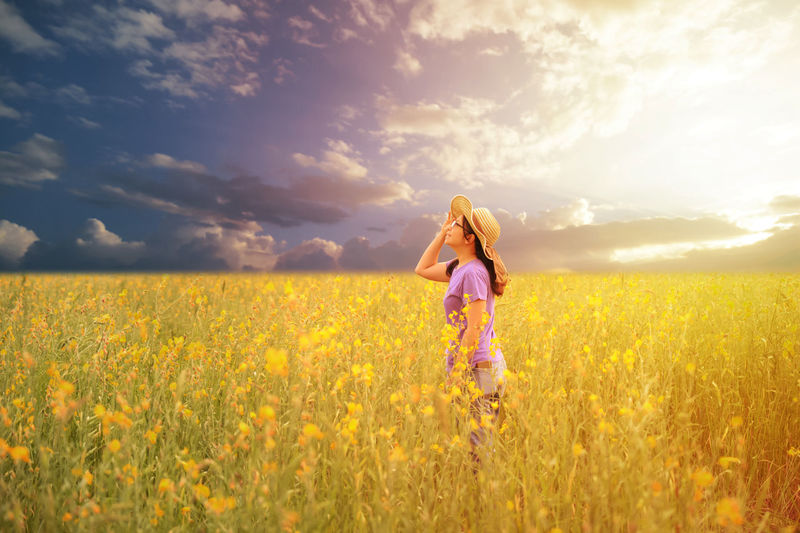 Happy asian woman standing and looing to sky in the yellow field Happiness Woman Agriculture Beauty In Nature Cloud - Sky Day Field Flower Girls Grass Growth Landscape Leisure Activity Lifestyles Nature One Person Outdoors People Plant Real People Rural Scene Scenics Sky Standing Yellow