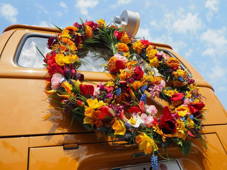 back of an orange hippie van with a flower power peace symbol Beauty In Nature Bouquet Car Close-up Cloud - Sky Day Flower Flower Arrangement Flower Head Flower Power🌼 Fragility Freshness Land Vehicle Mode Of Transport Multi Colored Nature No People Outdoors Petal Plant Sky Sunflower Transportation Vase Yellow