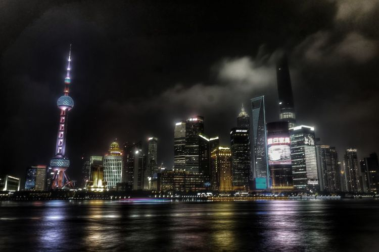 Huangpu River In Front Of Illuminated Oriental Pearl Tower And Buildings At Night