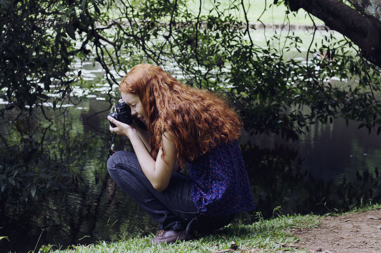 Side view of a woman photographing plants