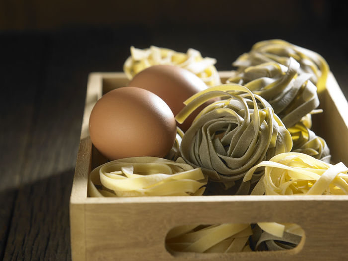 Directly above shot of tagliatelle pasta in crate on table