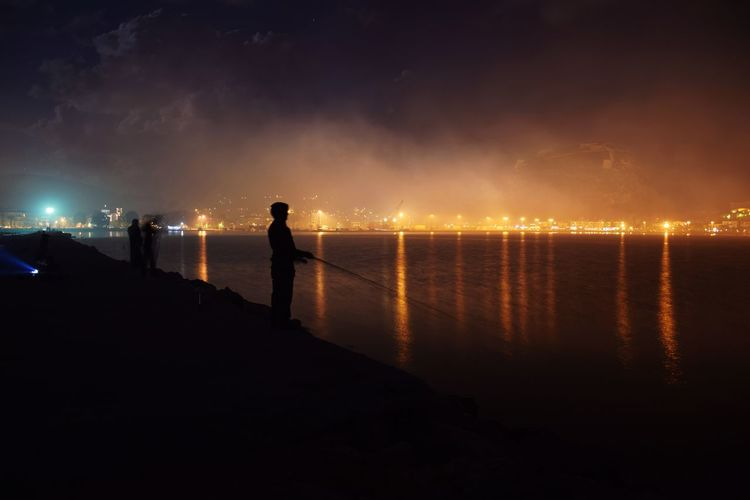 Silhouette man fishing by sea against cloudy sky at night