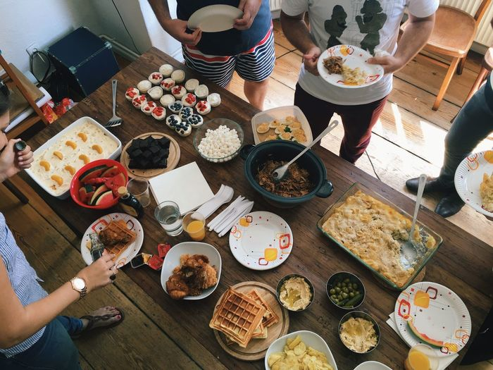 People Standing In Front Of Table Having Food At Home