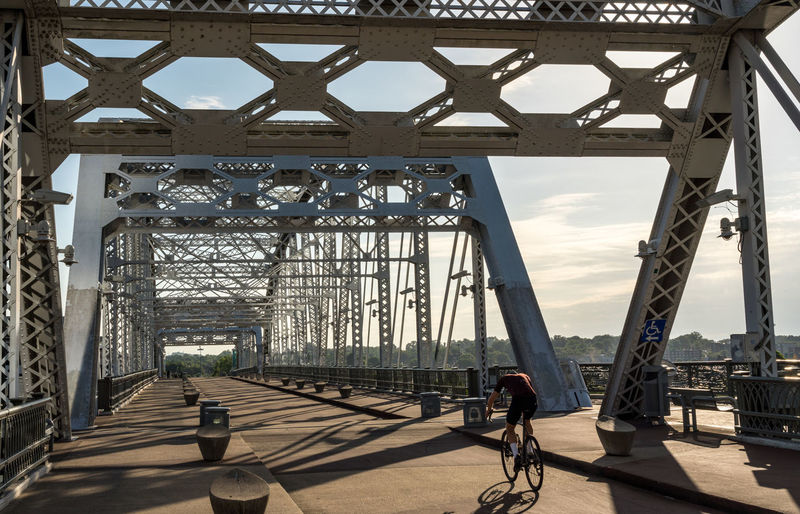 Man cycling on bridge