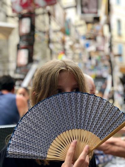 Girl holding hand fan at market