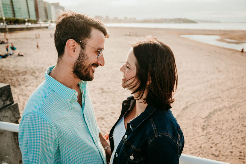 Couple embracing while standing on beach