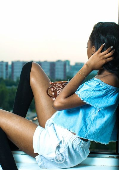 Side view of young woman having coffee while sitting on window sill