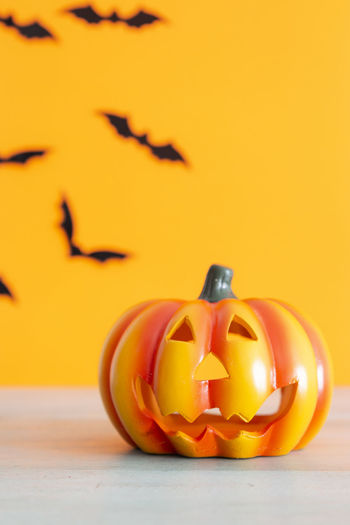 Close-up of jack o lantern on table against yellow wall