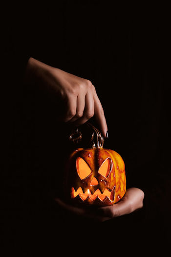Cropped image of person holding pumpkin against black background
