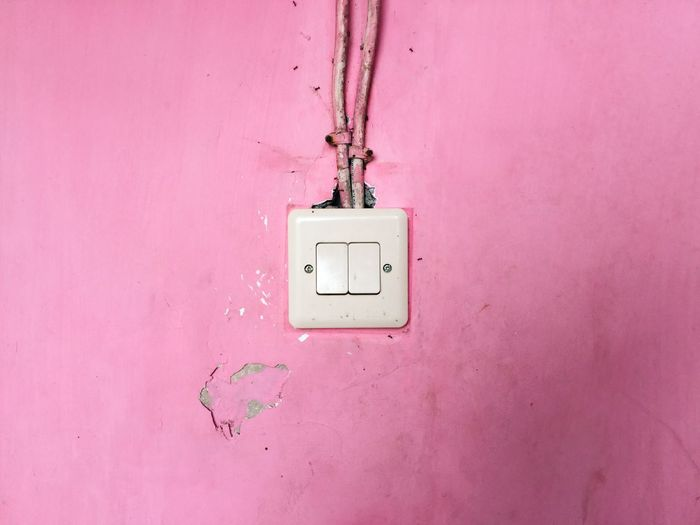 Close-Up Of White Electric Switch On Pink Wall