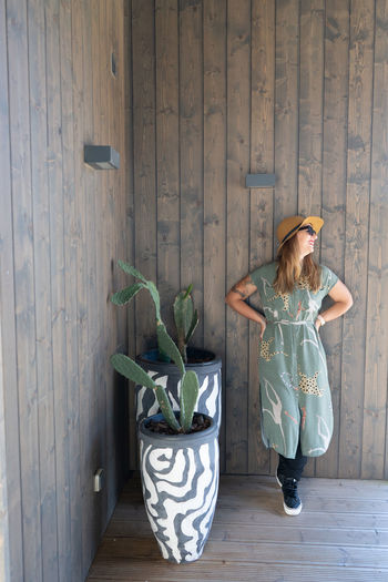 Woman with potted plants against wooden wall