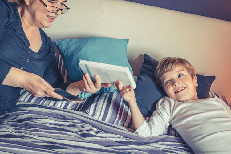 Grandmother Giving Book To Grandson On Bed At Home