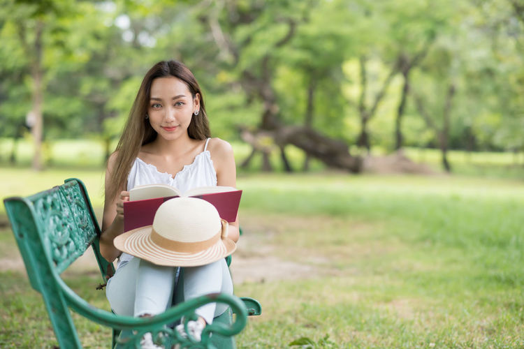 Portrait of smiling young woman reading book on field