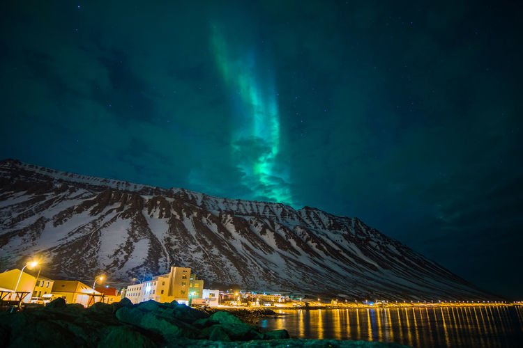Illuminated Buildings By Mountains Against Sky With Aurora Borealis