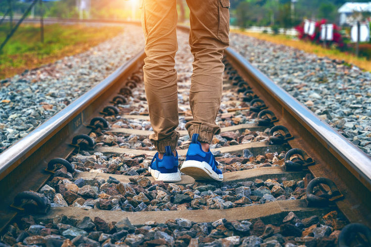 Feet of male walking on railroad. Travel concept. Rail Transportation Track Railroad Track Low Section One Person Transportation Body Part Shoe Day Standing Human Body Part Human Leg Solid Sunlight Limb Gravel Nature Stone - Object Men Human Limb Outdoors Pebble Human Foot Jeans