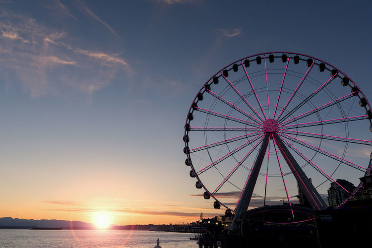 Seattle waterfront at sunset with Great wheel Ferris wheel with solar flare and lights. Elliott Bay Seattle Sky And Clouds Sunburst Tourist Attraction  Travel Amusement Park Amusement Park Ride Arts Culture And Entertainment Cruise Ferris Wheel Fine Art Golden Hour Lens Flare Nature No People Orange Color Outdoors Sky Sunset Tourism Transportation Vacation Water Waterfront