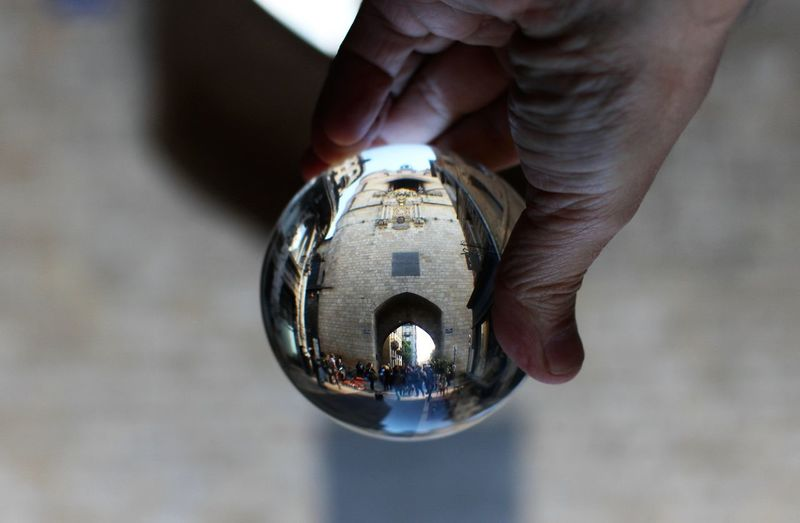 Cropped hand holding crystal ball building reflection