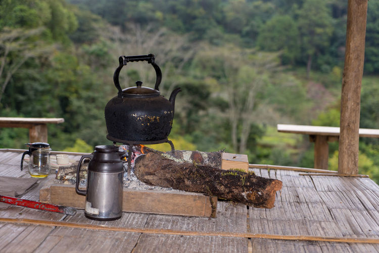 Close-up of tea kettle on stove against trees