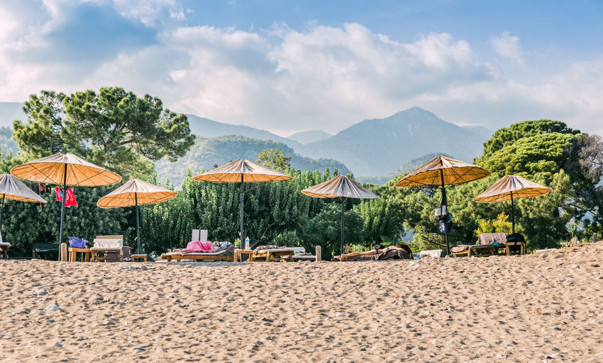 Beach umbrellas on Turkish Riviera in Cirali, Antalya Province, Turkey, Asia People Incidental People Sunbathing Lying Down Beachphotography Beach Photography Beach Life Life Is A Beach Türkiye Mediterranean  Tourism Beach Umbrella Umbrella Deck Chair Medium Group Of Objects Low Angle View Vacations Relaxing Towel Tranquility çıralı Antalya Women Napping Sleeping Land Beach Sand Sky Cloud - Sky Beauty In Nature Parasol Nature Scenics - Nature Day Mountain Thatched Roof Tranquil Scene Tree Sunshade Chair Outdoors