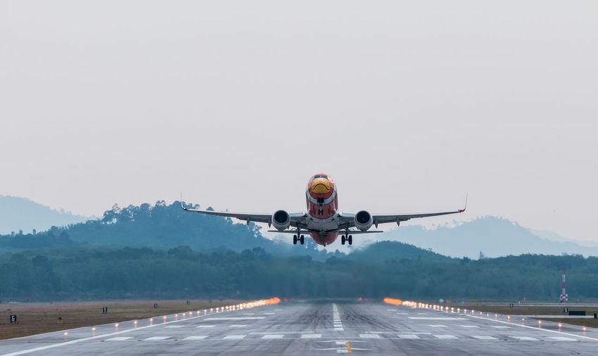 Airplane taking off on runway against sky