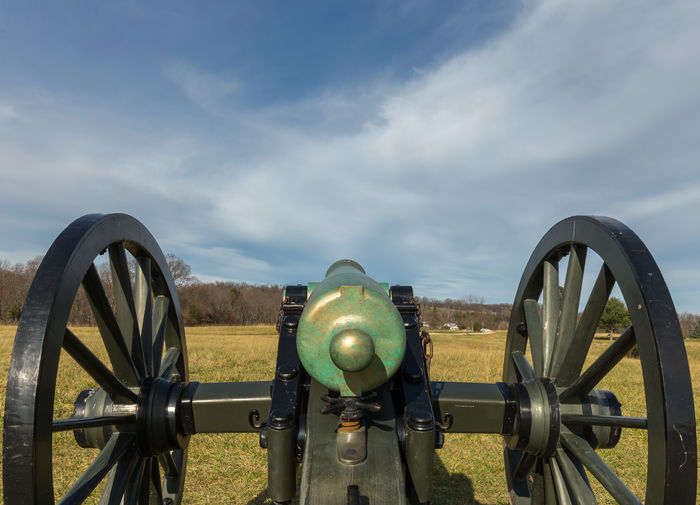 Cannon On Field Against Cloudy Sky