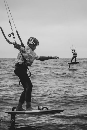Full length of man and woman in sea against sky