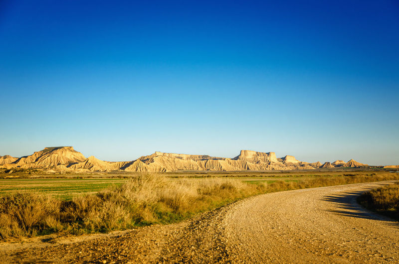 Scenic view of road amidst field against clear blue sky, bardenas reales, spain