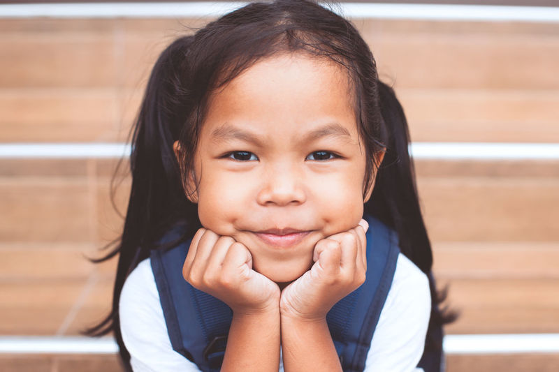 Close-up portrait of cute smiling girl with hands on chin