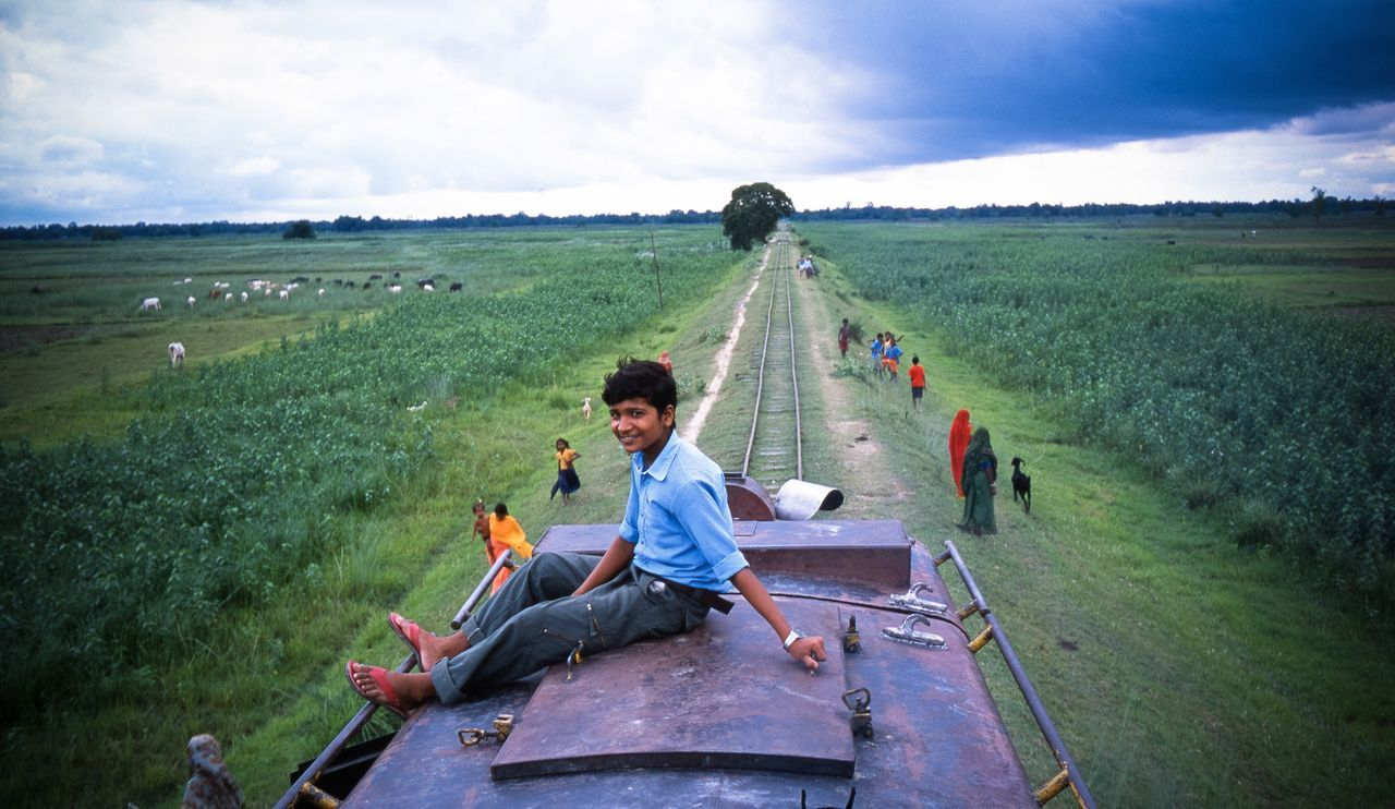 Portrait of young man sitting on train against cloudy sky
