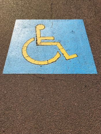 Painted sign on the ground to indicate a parking spot reserved for people with a disability. Disabled Parking Space Disabled Parking Spot Disabled Parking Sign Communication Disabled Sign Disabled Access Representation Human Representation High Angle View Differing Abilities Symbol Information No People Wheelchair