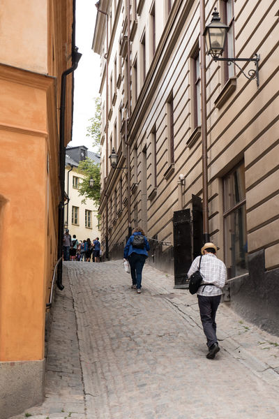 Architecture Building Exterior Built Structure City City Life Day Diminishing Perspective Footpath Full Length Gamla Stan Men Outdoors Person Rear View Residential Structure Steep Street The Way Forward Walking