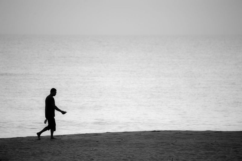 Silhouette man walking on beach against sky