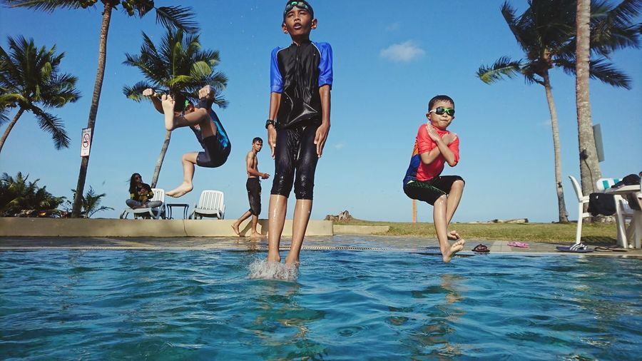 Jump Visual Creativity Tree Water Child Full Length Swimming Pool Togetherness Happiness Childhood Blue Palm Tree